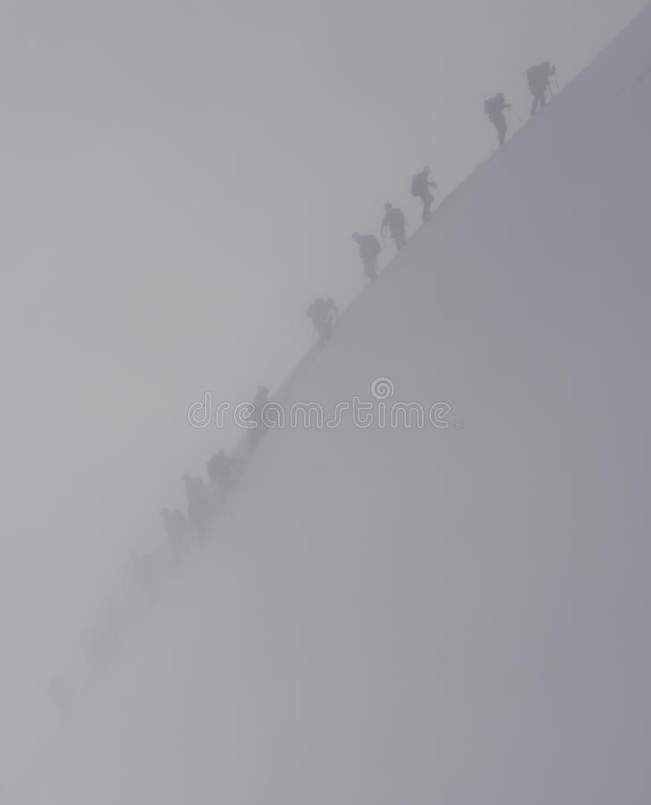 Climbers in snowstorm stock photos