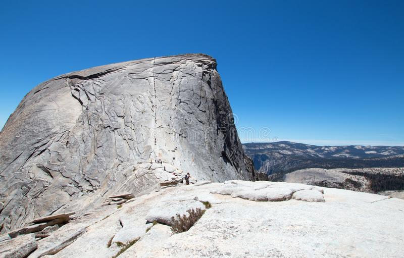 Climbers using cables to ascend Half Dome as seen from the Sub Dome in Yosemite National Park in California USA royalty free stock images