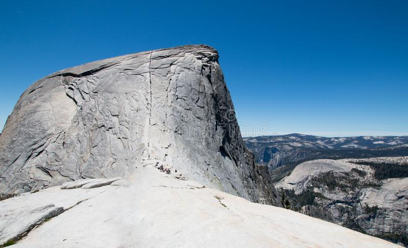 Climbers using cables to ascend Half Dome as seen from the Sub Dome in Yosemite National Park in California USA stock image
