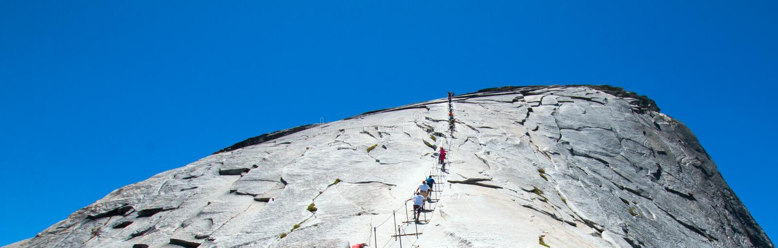 Climbers using cables to ascend Half Dome in Yosemite National Park in California USA royalty free stock photo