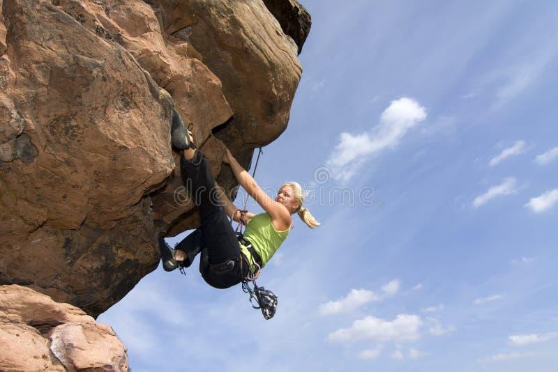 Climbig da mulher nova uma rocha fotografia de stock royalty free