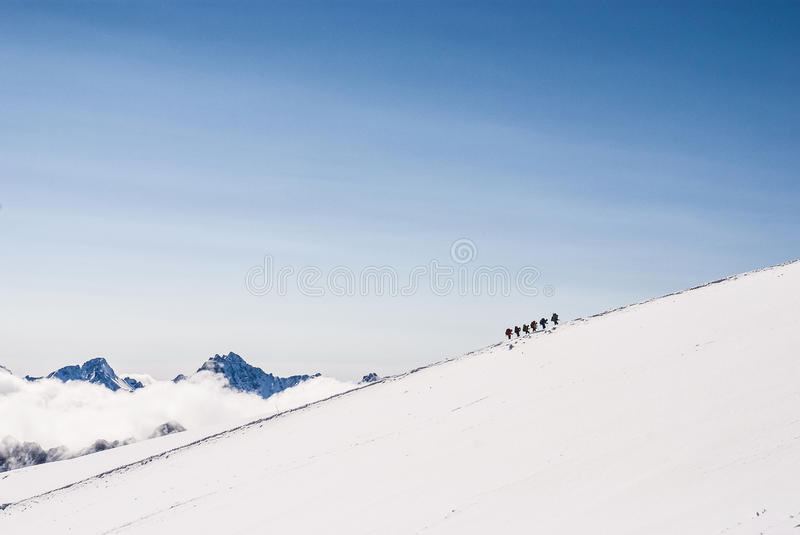 Climbing climbers on the snowy mountain top. Dream line royalty free stock photography