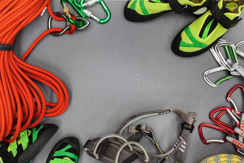 Climbing equipment laid out on on a black background. Rope, climbing shoes, chalk bag, quickdraws, belay, rappel device with carab royalty free stock image