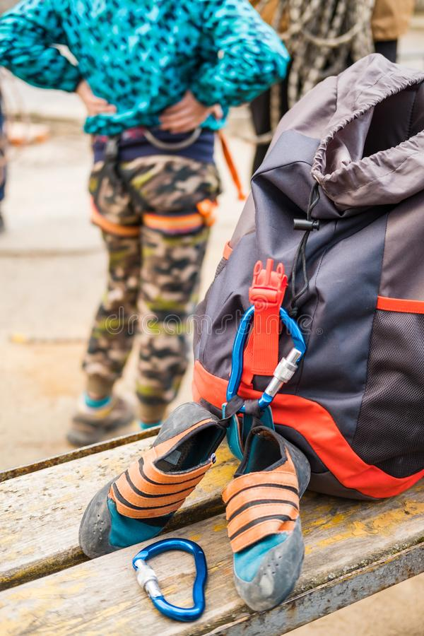 Climbing equipment ropes carbines backpacks suspension for sitting climber and special shoes for rock climbing royalty free stock image