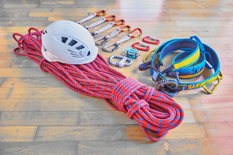 Climbing equipment on wooden background: red dynamic rope with blue stripes, helmet, blue/yellow harness, quickdraws, belay device royalty free stock photography