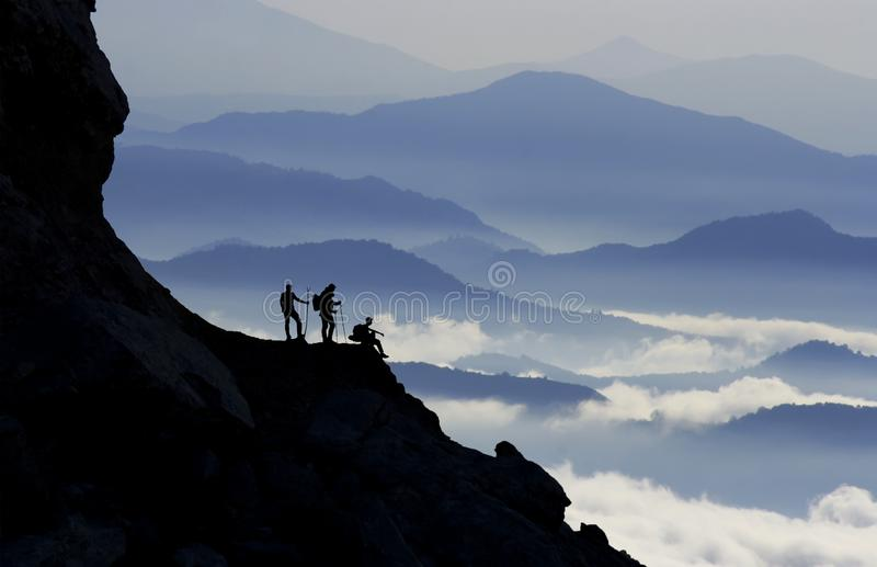 Mountain Climbers Reaching A Summit. A silhouette of mountain climbers reaching a summit royalty free stock photography