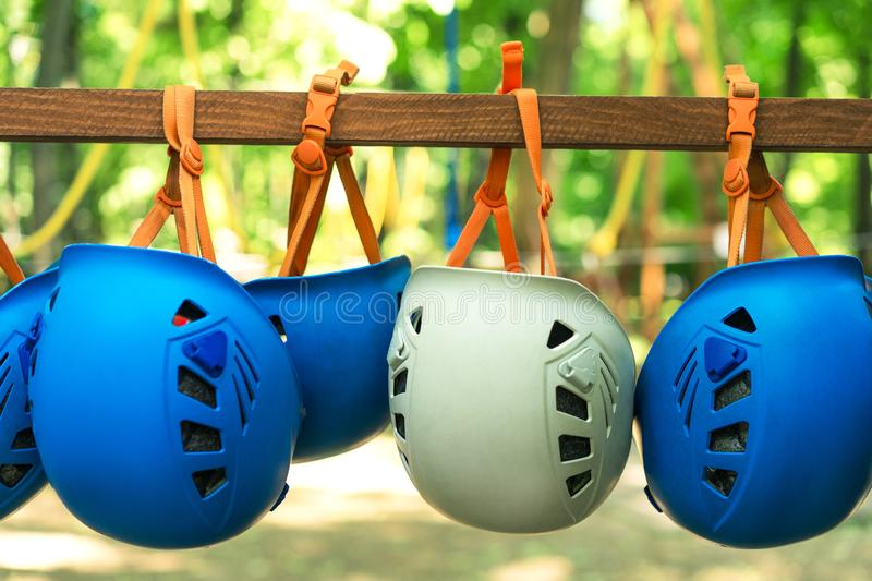 Climbing gear equipment - blue and white helmet hanging on a board in a rope park royalty free stock images