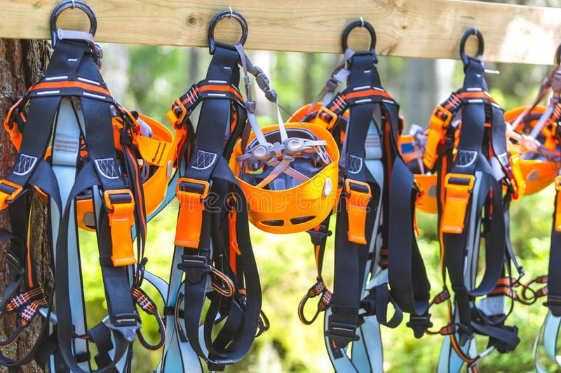 Climbing gear equipment - orange helmet harness zip line safety equipment hanging on a board. Tourist summer time adventure park royalty free stock images