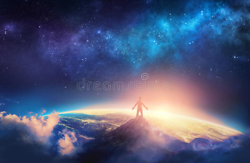 Climbing a high mountain. A man climbs a high mountain and lifts his arms up in praise stock image