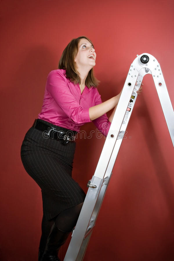 Climbing the Ladder. A young woman climbs a ladder over a red background royalty free stock photos