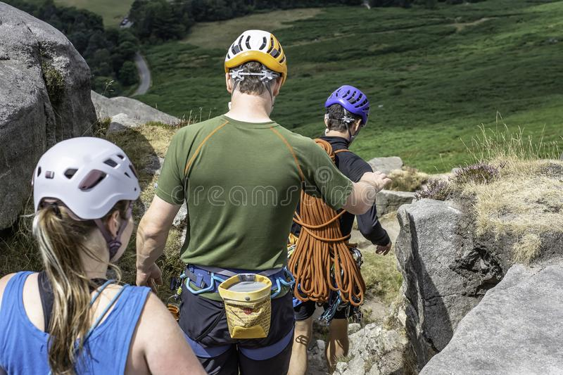 Climbing learners following their climbing instructor in rough t stock images