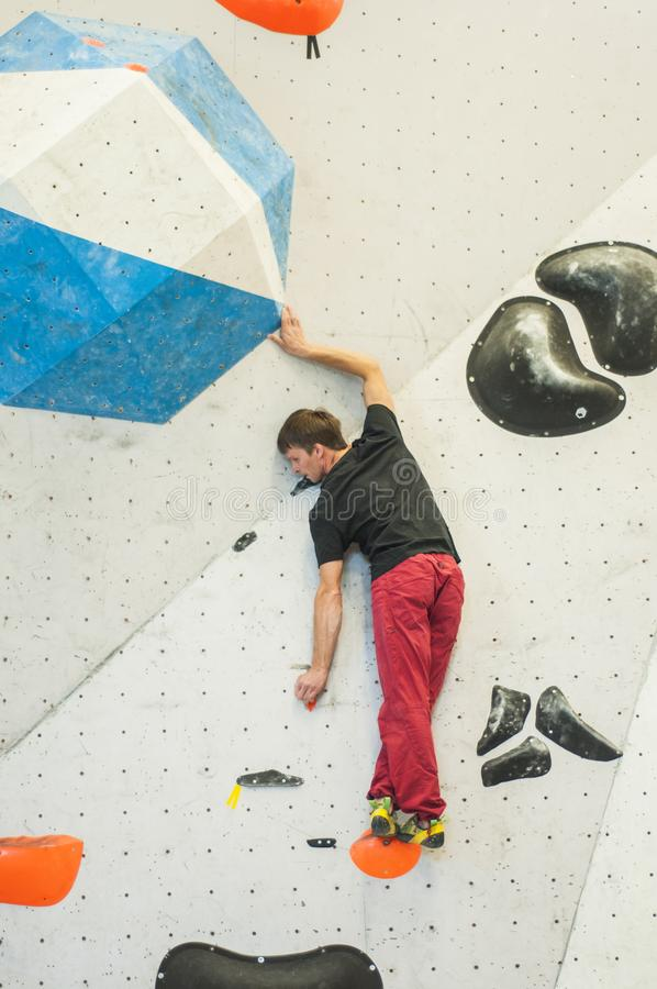 Climber in a boulder gym. Man climbing bouldering problem. Colorful volumes and holds on a white wall. stock photos