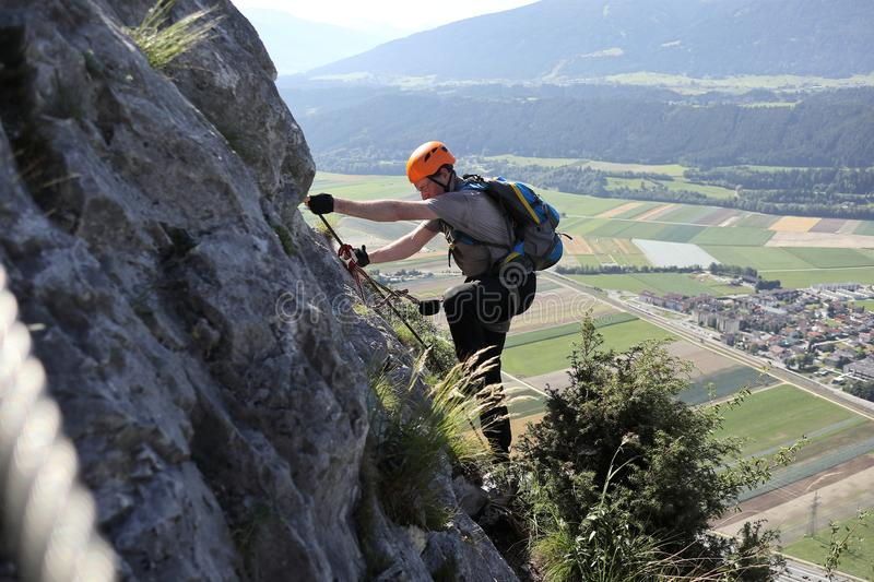 Climbing man with equipment. Is on a rock wall stock photography