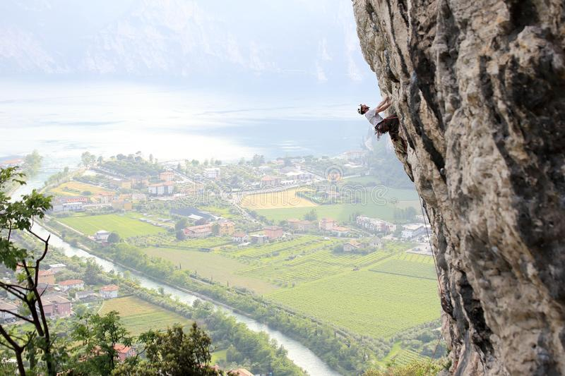 Climbing man on a high rock wall. In front of garda lake royalty free stock photography