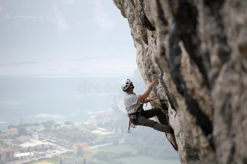 Climbing man on a stone wall stock image