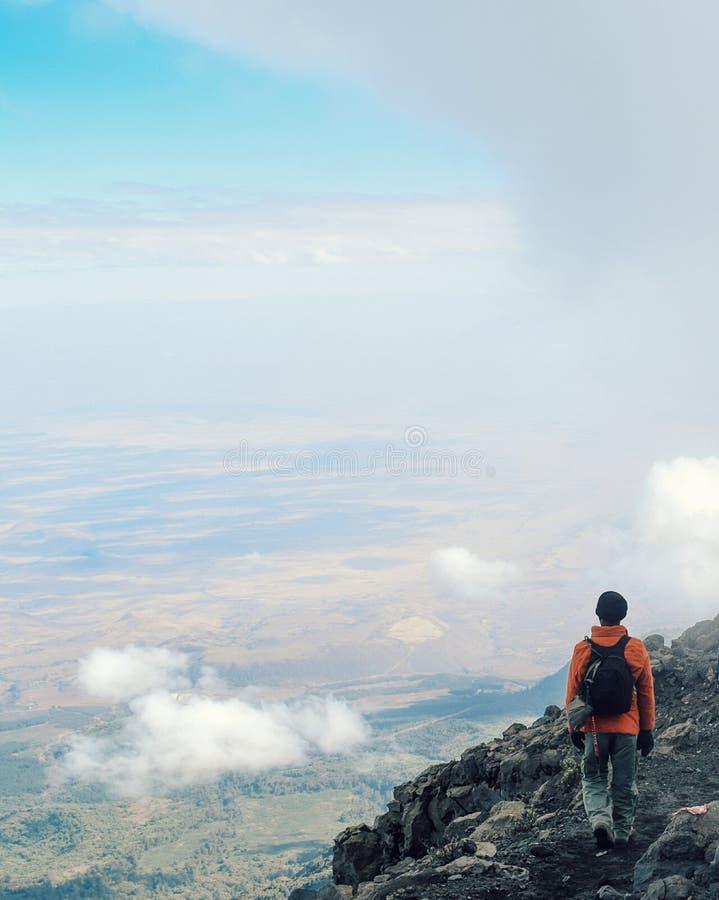 Climbing Mount Meru, Arusha National Park, Tanzania. A group of hikers above the clouds descending from the summit of Mount Meru, Arusha National Park, Tanzania stock images