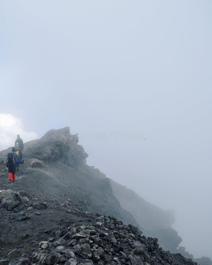 Climbing Mount Meru, Arusha National Park, Tanzania. A group of hikers above the clouds descending from the summit of Mount Meru, Arusha National Park, Tanzania stock image