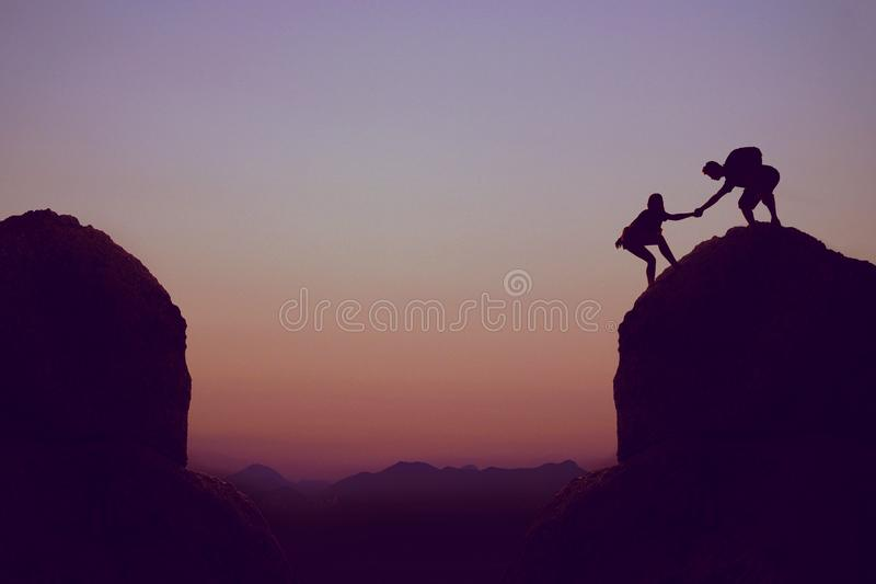 Climbing people in mountains as symbol for team spirit stock photography
