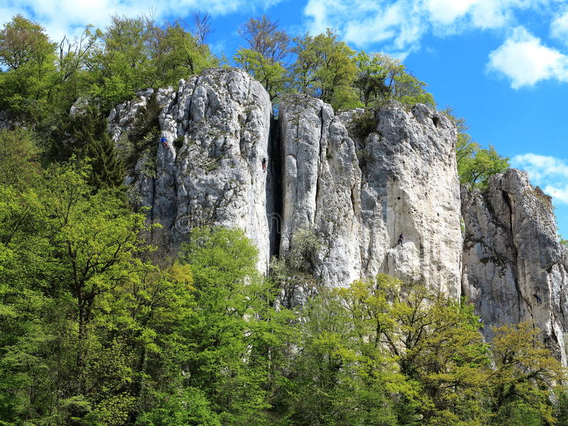 Climbing rock landscape with climbers in Danube gorge. Rock climbers practice on a rock in the nature reserve Weltenburger Enge - a gorge of the Danube river in royalty free stock image