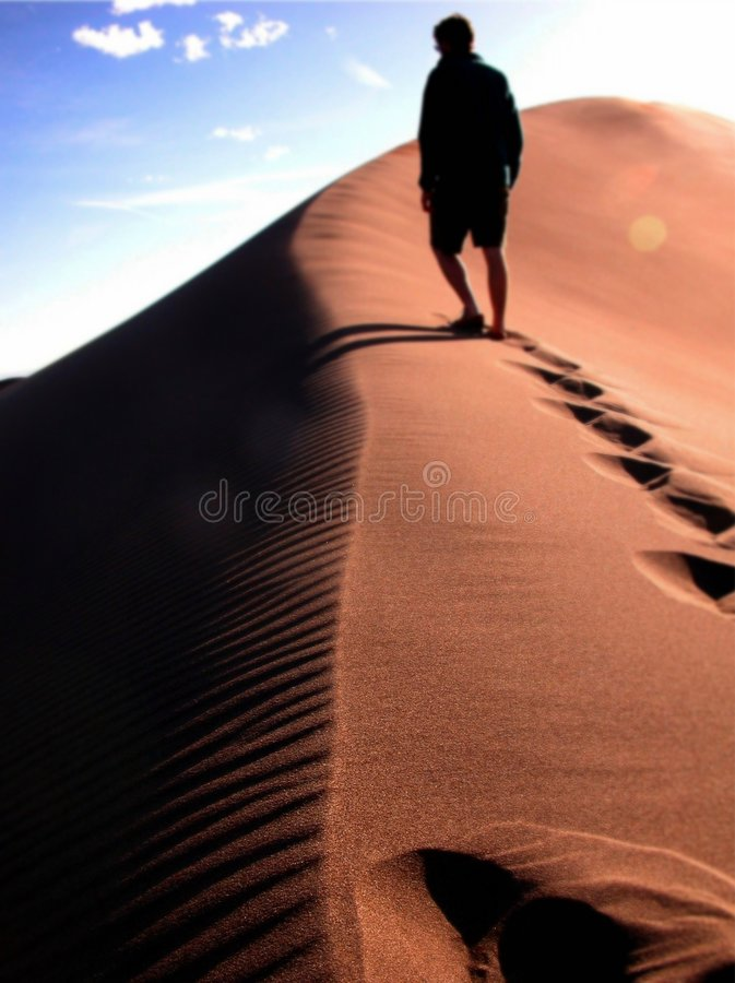 Climbing a sand dune in colorado royalty free stock image