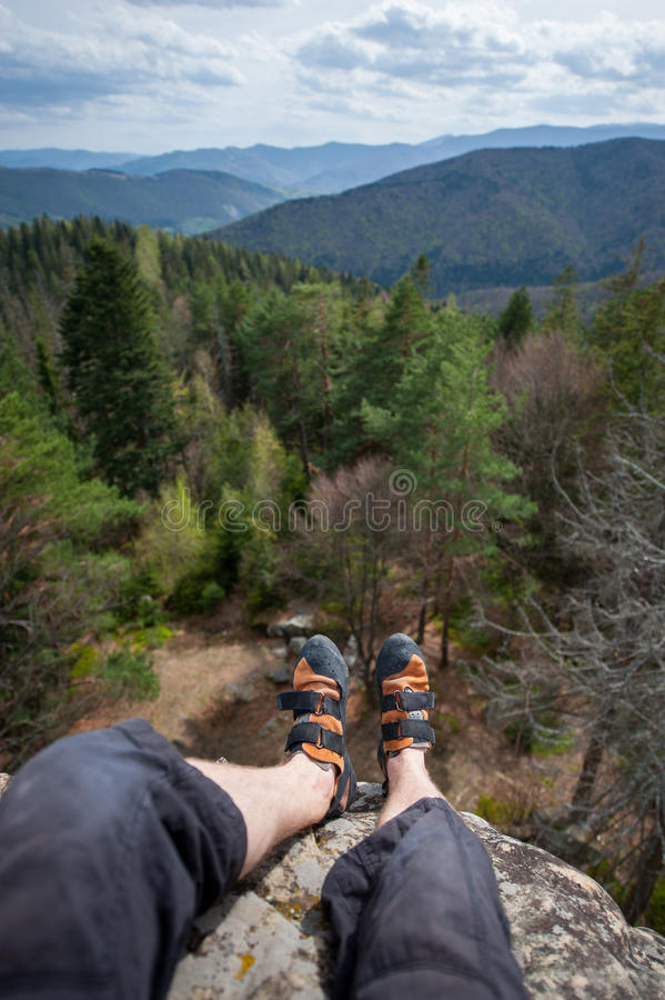 Climbing shoes. Focus an astonishing view mountain and forest valley at day with legs and feet in first, freedom concept. Climbing shoes. Wide angle lens royalty free stock photography