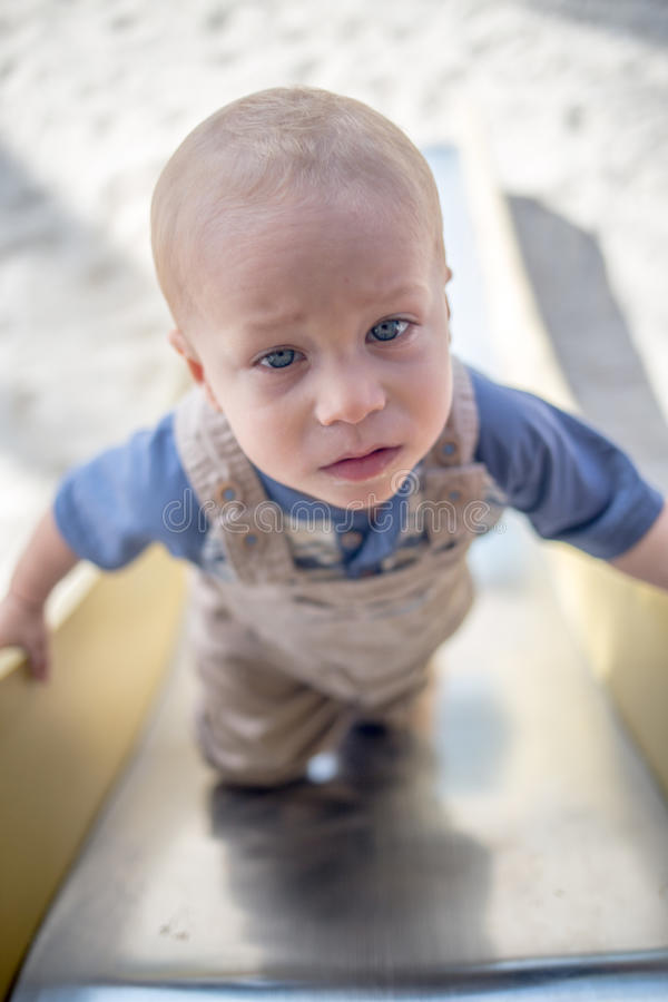 Climbing The Slide. A Little blue eyed Baby Boy Climbs the slide at a beach playground stock images