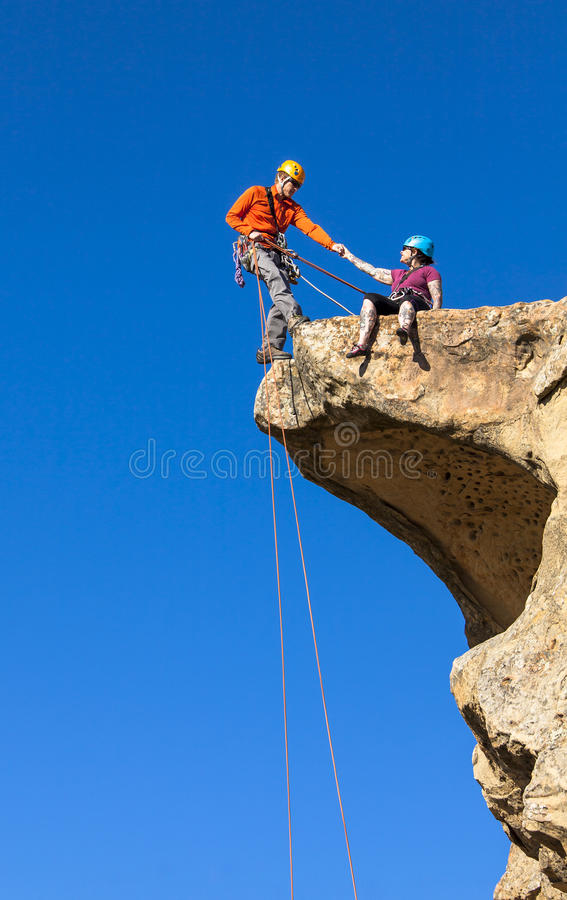 Climbing team struggles to the summit. royalty free stock images