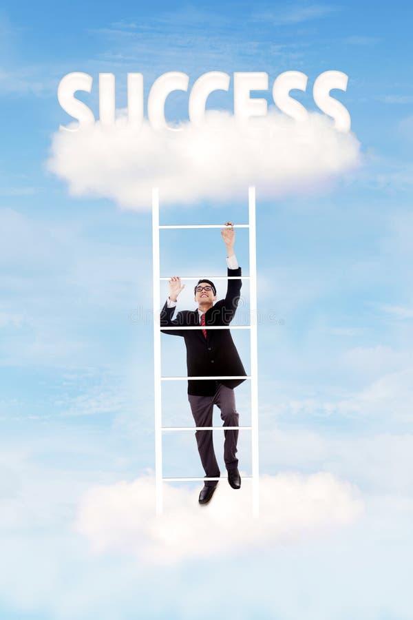 Climbing upward to success. Businessman climbing upward on the stair of cloud to get success stock photo