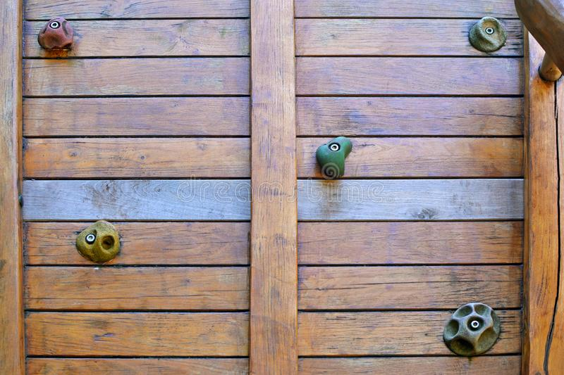 Climbing wall made out of wooden planks with different shaped grips for hands and feet. Climbing wall made out of wooden planks with different shaped climbing stock photo
