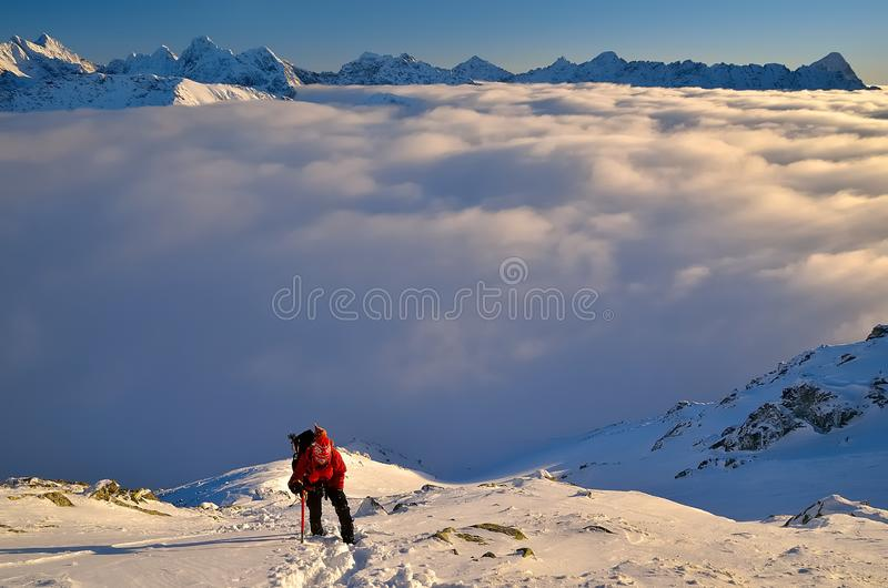 Climbing in winter mountains. Hiking and climbing on snow in high High Tatras in Poland with summits over clouds in the background