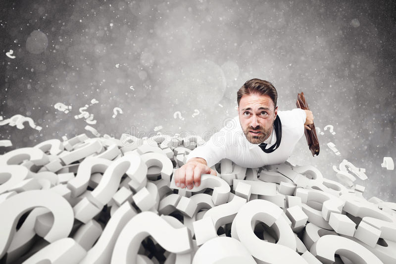 Clinging to the doubts. Afraid businessman clinging to question marks pile stock photo