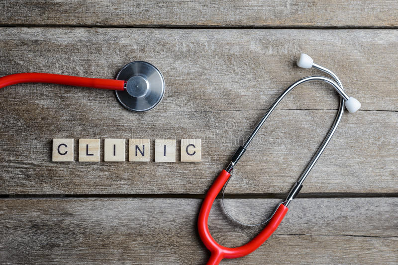 Clinic text word made with wood blocks and Red Heart,stethoscope on wooden table stock photography