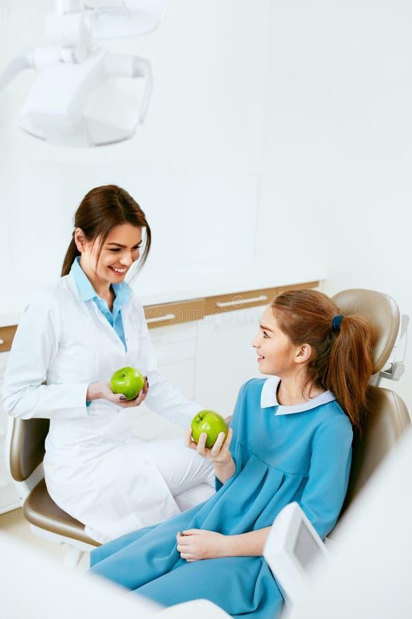 Clinica dentale Dentista femminile And Little Patient che mangia Apple immagine stock libera da diritti