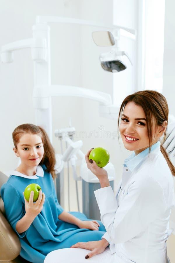 Clinica dentale Dentista femminile And Little Patient che mangia Apple immagini stock libere da diritti