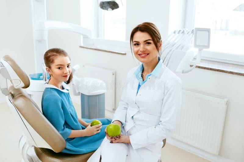 Clinica dentale Dentista femminile And Little Patient che mangia Apple immagine stock