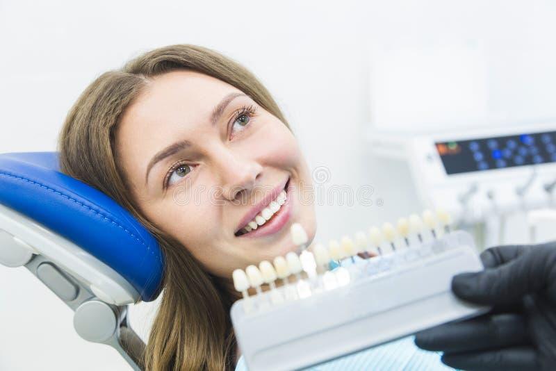 Clinica dentale Ricezione, esame del paziente Cura dei denti Dentista con i campioni di colore del dente che scelgono ombra per fotografie stock