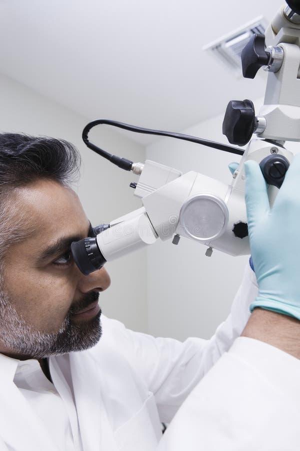 Clinica di Using Microscope In del dentista fotografia stock