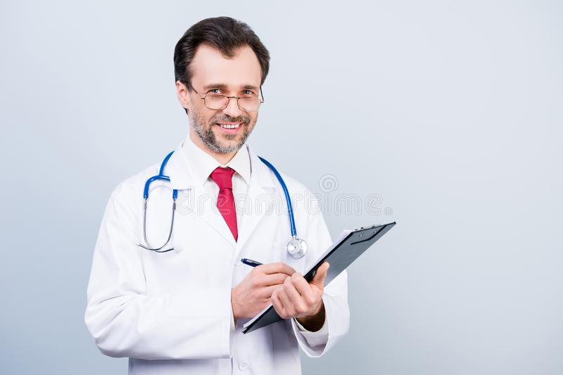 Clinical occupation medico equipment professional qualified doctor holding clipboard writing prescription with pen wearing formal royalty free stock photos