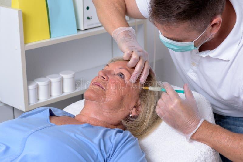 Clinicien masculin injectant sur le visage d'une femme images libres de droits
