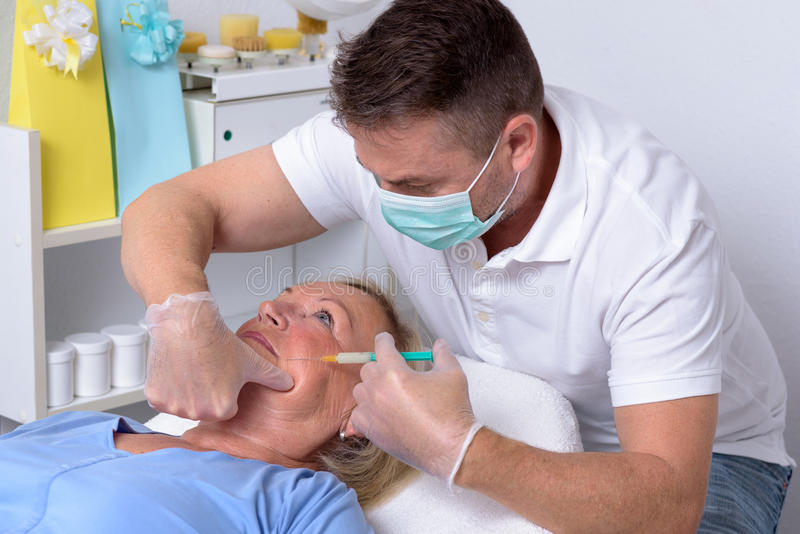 Clinicien masculin injectant sur le visage d'une femme images stock