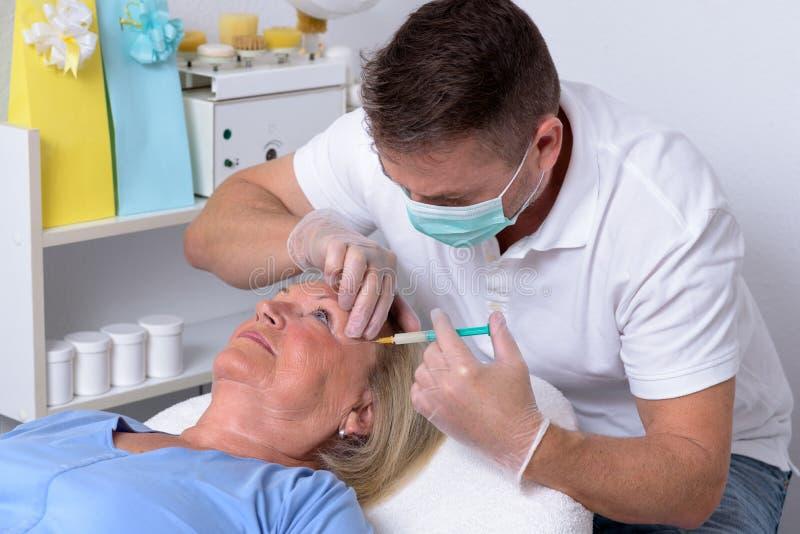 Clinicien masculin injectant sur le visage d'une femme photo libre de droits