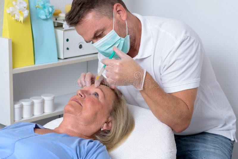 Clinicien masculin injectant sur le visage d'une femme photos stock