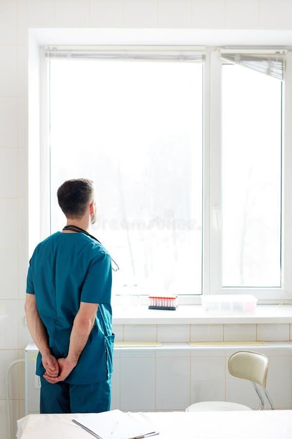 Clinicien par la fenêtre photo stock