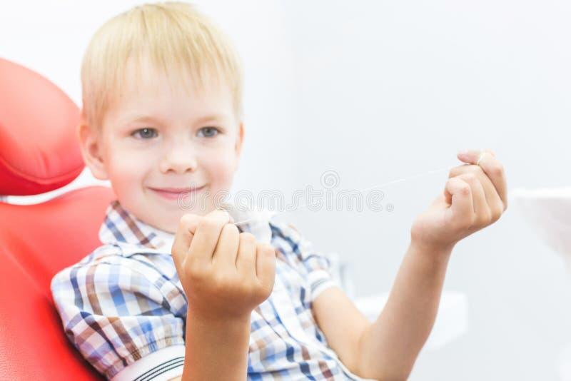 Clinique dentaire R?ception, examen du patient Soin de dents Un petit gar?on avec le fil dentaire s'assied dans une chaise dentai photos stock