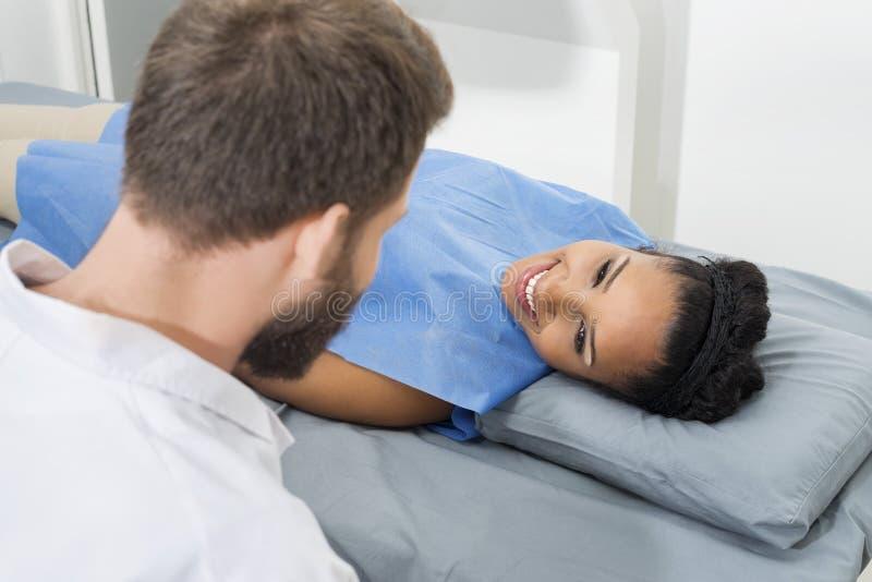 Clinique masculine de regard patiente femelle de docteur Examining Her In image stock