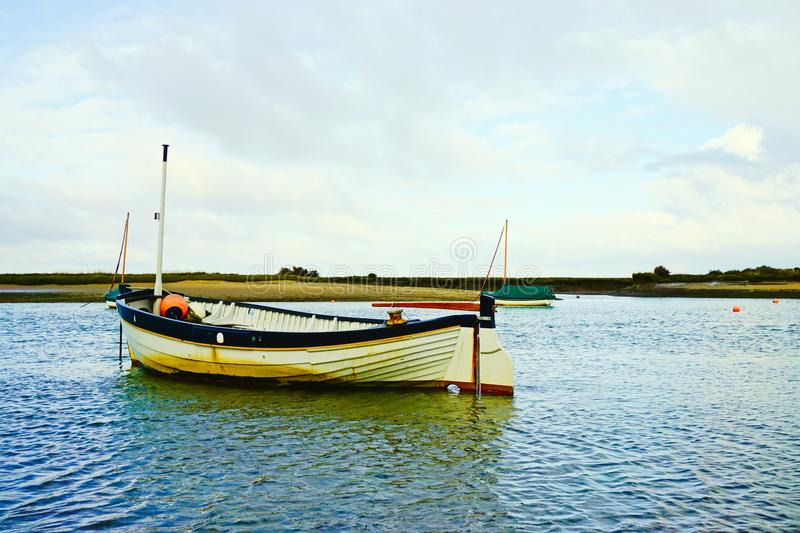 Clinker fishing dinghy. Small clinker built fishing dinghy in Burnham Overy Staithe harbour royalty free stock image