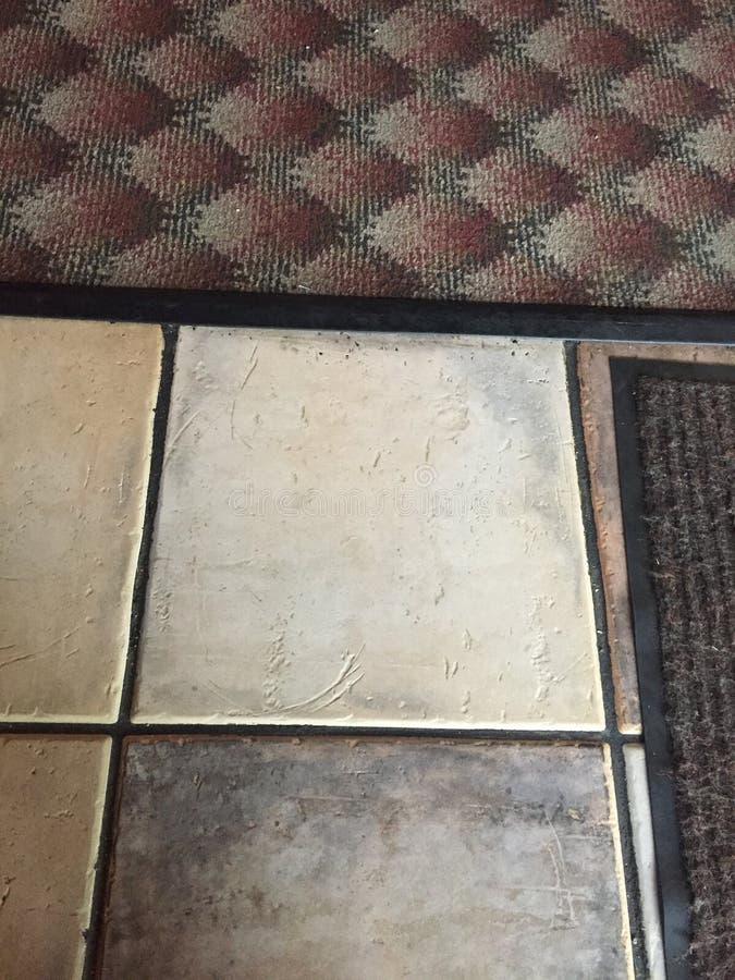 Clinker floor with two doormats on. A grey black doormat and a red grey black doormat against the grey white floor stock image