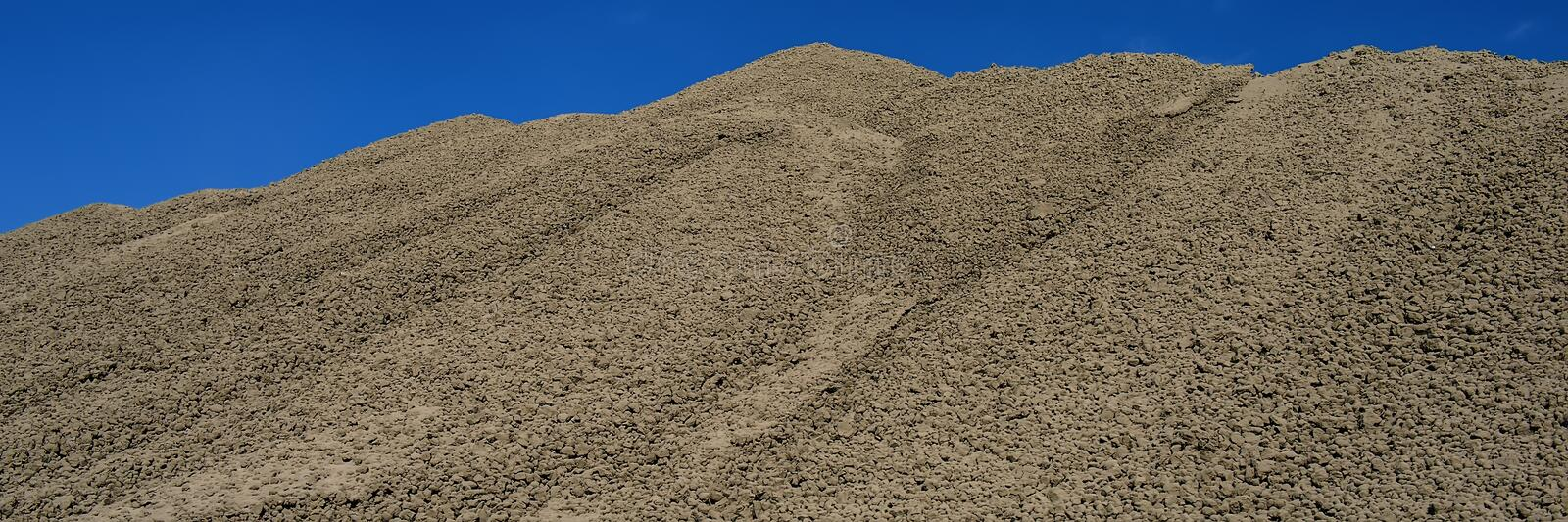 Clinker surface in a raw material warehouse and blue sky, cement production. Web banner for your design stock photo