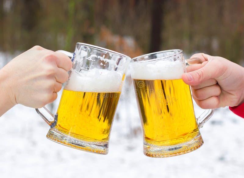 Clinking стекла пива на предпосылке леса зимы стоковые фотографии rf