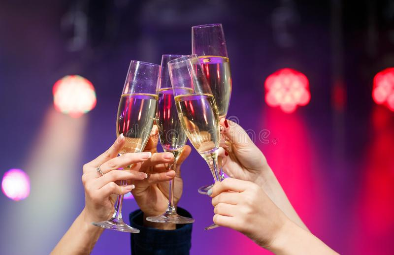 Clinking glasses of champagne in hands on bright lights background. stock images